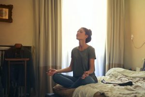 Person sitting on bed meditating
